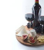 Two glasses of red wine, goat cheese and fig. On white background Royalty Free Stock Images