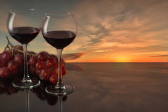 Two glasses of red wine with grapes against the background of a fiery sunset Stock Photos