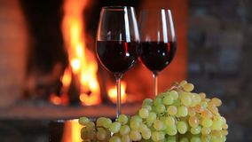 Two glasses of red wine with grapes near the fireplace in the evening. Two glasses of red wine with grapes near the fireplace stock video footage