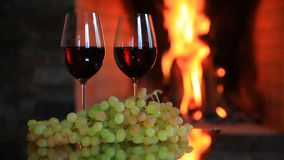 Two glasses of red wine with grapes near the fireplace in the evening. Two glasses of red wine with grapes near the fireplace stock footage