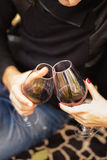 Two glasses of the red wine in hands, picnic theme royalty free stock photo