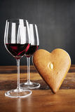 Two glasses of red wine and heart-shaped gingerbread Stock Photo