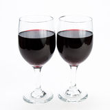 Two glasses of red wine on isolating background. Two romantic glasses of red wine next to each other on white isolating background Stock Photography