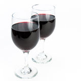 Two glasses of red wine on isolating background. Two glasses of romantic red wine one standing in front of the other on white isolating background Royalty Free Stock Photography