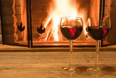 Two glasses of red wine near cozy fireplace, in country house, winter vacation, horizontal. Tranquil scene before cozy fireplace, with two glasses of red wine stock image