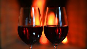 Two glasses of red wine near a fireplace.  stock video footage