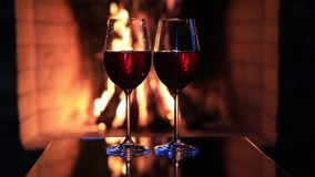 Two glasses of red wine near a fireplace.  stock video