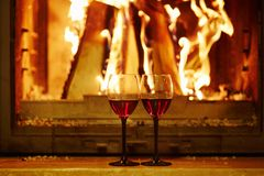 Two glasses of red wine near fireplace. Cozy romantic evening for couple or Christmas celebration concept Stock Photo