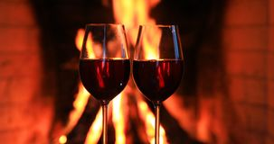 Two glasses of red wine near a fireplace. 4K video stock video