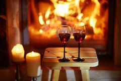 Two glasses of red wine near fireplace royalty free stock photography