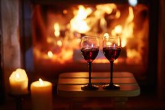 Two glasses of red wine near fireplace royalty free stock images