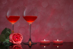Two glasses of red wine with a rose and candles Royalty Free Stock Photography