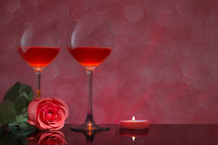 Two glasses of red wine with a rose and candles Stock Images