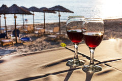 Two glasses of red wine with sun reflection, sea Royalty Free Stock Images