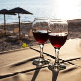Two glasses with red wine and Sunset on beach  at the background Royalty Free Stock Photo
