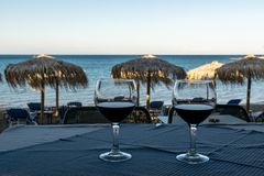 Two glasses of red wine on a table at sunset on beach stock photo