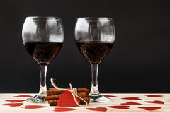 Two glasses of red wine and tied cinnamon sticks with red hearts around Stock Photo