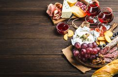 Delicatessen plate. Two glasses of red wine, wooden board, cold meat, cheese, fruit, dip. Wooden background. Space for text. Delicatessen plate. Mix of different Stock Image