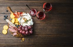 Delicatessen plate. Two glasses of red wine, wooden board, cold meat, cheese, fruit, dip. Wooden background. Space for text. Delicatessen plate. Mix of different Stock Photo