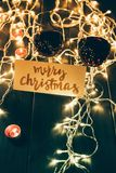 Wineglasses and merry christmas card. Two glasses with red wine on wooden table with fairylights, candles and merry christmas card Royalty Free Stock Photos