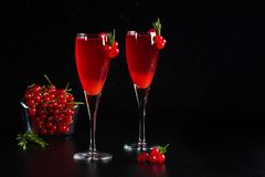Two glasses redcurrant wine drink juice decorated with rosemary. Two glasses of redcurrant wine drink juice decorated with rosemary and berries, a cup of royalty free stock photos