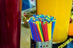 Two glasses with refreshing summer drinks, cold fresh cherry and orange lemonade juices, and colorful drinking straws stock photography