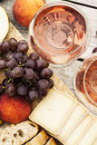 Two glasses of rose wine and board with fruits, bread and cheese Royalty Free Stock Photos