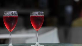 Two glasses of rose wine dark background stock video footage