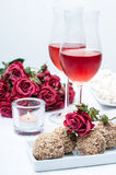 Two glasses of rose wine , fresh flowers, cakes Stock Photo