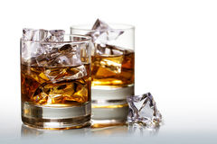 Two glasses of scotch whiskey with ice cubes, background fades t. O white, copy space Royalty Free Stock Photography