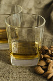 Two glasses of scotch whiskey on wool sack with almond seeds Royalty Free Stock Image