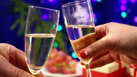 Two glasses with shompansky are baked close-up on the table with gifts on the New Year`s background with herlands. Shooting with dolly from right to left stock footage
