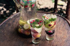 Two glasses of soft drink with a splash and spray water seasonal fruit stand on the wooden surface of the table in the garden besi Stock Photography