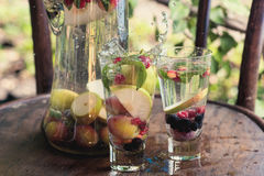 Two glasses of soft drink with a splash and spray water seasonal fruit stand on the wooden surface of the table in the garden besi Royalty Free Stock Photography
