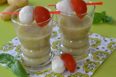 Two glasses of soup. Basil potato soup served in small glasses with skewers of tomato and mozzarella Stock Photo