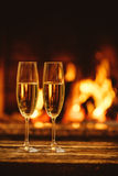 Two glasses of sparkling champagne in front of warm fireplace. C Royalty Free Stock Photography