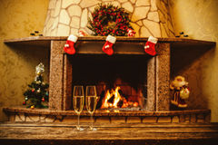 Two glasses of sparkling champagne in front of warm fireplace. C Stock Photo