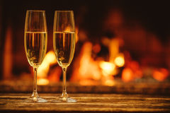 Two glasses of sparkling champagne in front of warm fireplace. C Royalty Free Stock Images