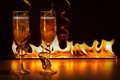 Two glasses of sparkling champagne with golden ribbons against the bokeh background of bright flames creating a cozy. Festive atmosphere of holyday Christmas or stock images