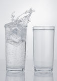 Two glasses with sparkling and still splash water Stock Photography