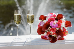 Two glasses of sparkling wine and bouquet of the bride Royalty Free Stock Photo