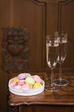 Two glasses of sparkling wine or champagne with small colorful macaroons. On wooden table Stock Images