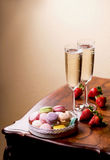 Two glasses of sparkling wine or champagne with small colorful macaroons Royalty Free Stock Image