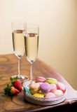 Two glasses of sparkling wine or champagne with small colorful macaroons Stock Photo
