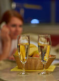 Two glasses of sparkling wine in hotel room with woman in backgr Stock Photo