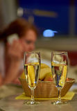 Two glasses of sparkling wine in hotel room with woman in backgr Royalty Free Stock Images
