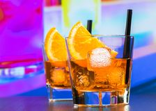 Two glasses of spritz aperitif aperol cocktail with orange slices and ice cubes on bar table, disco atmosphere background Royalty Free Stock Photo