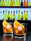 Two glasses of spritz aperitif aperol cocktail with orange slices and ice cubes on bar table, disco atmosphere background Stock Photos