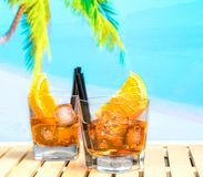 Two glasses of spritz aperitif aperol cocktail with orange slices and ice cubes on blur beach background Stock Photo