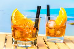 Two glasses of spritz aperitif aperol cocktail with orange slices and ice cubes on blur beach background Royalty Free Stock Photo